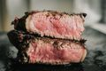 two slices of a rare steak stacked on top of each other