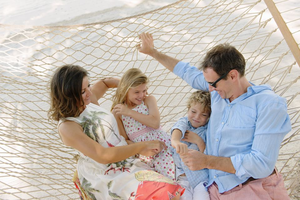 Family relaxing in beach hammock, Providenciales, Turks and Caicos Islands, Caribbean