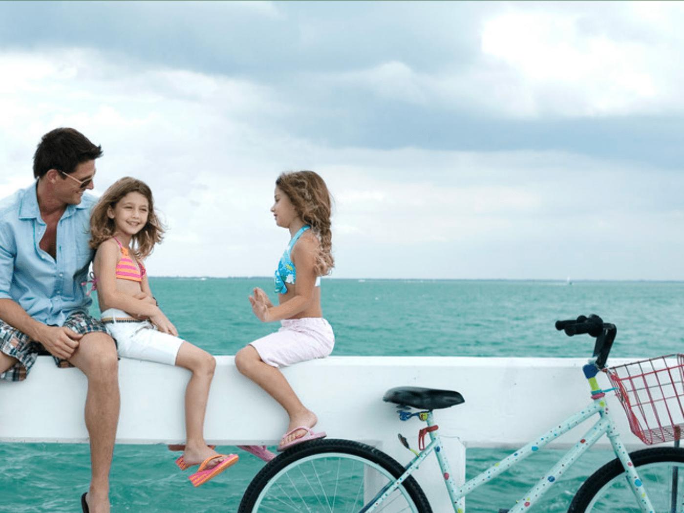 Un padre y sus hijas en un muelle con una bicicleta
