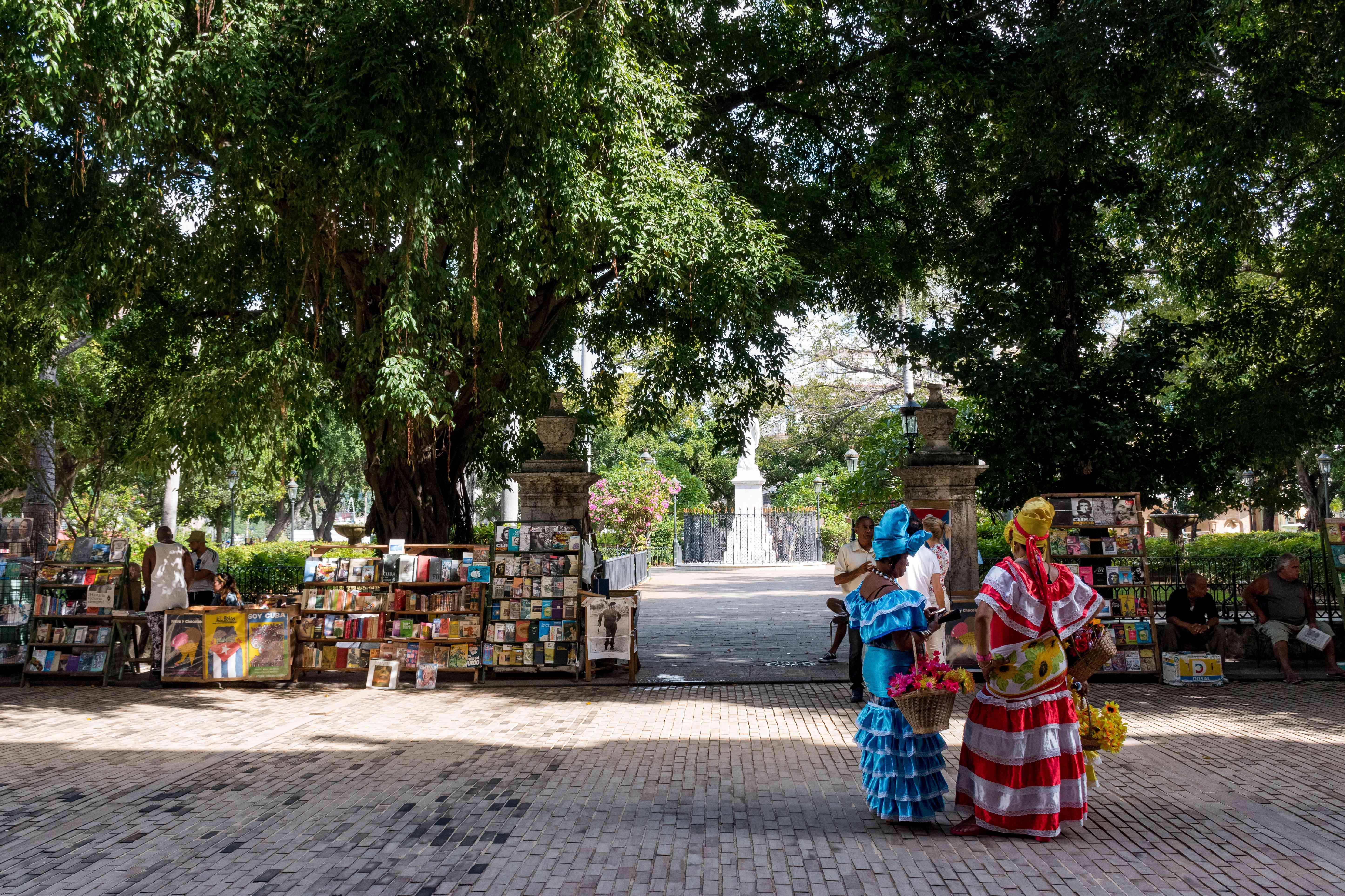 Two women in traditionally colorful outfits walking through old havana