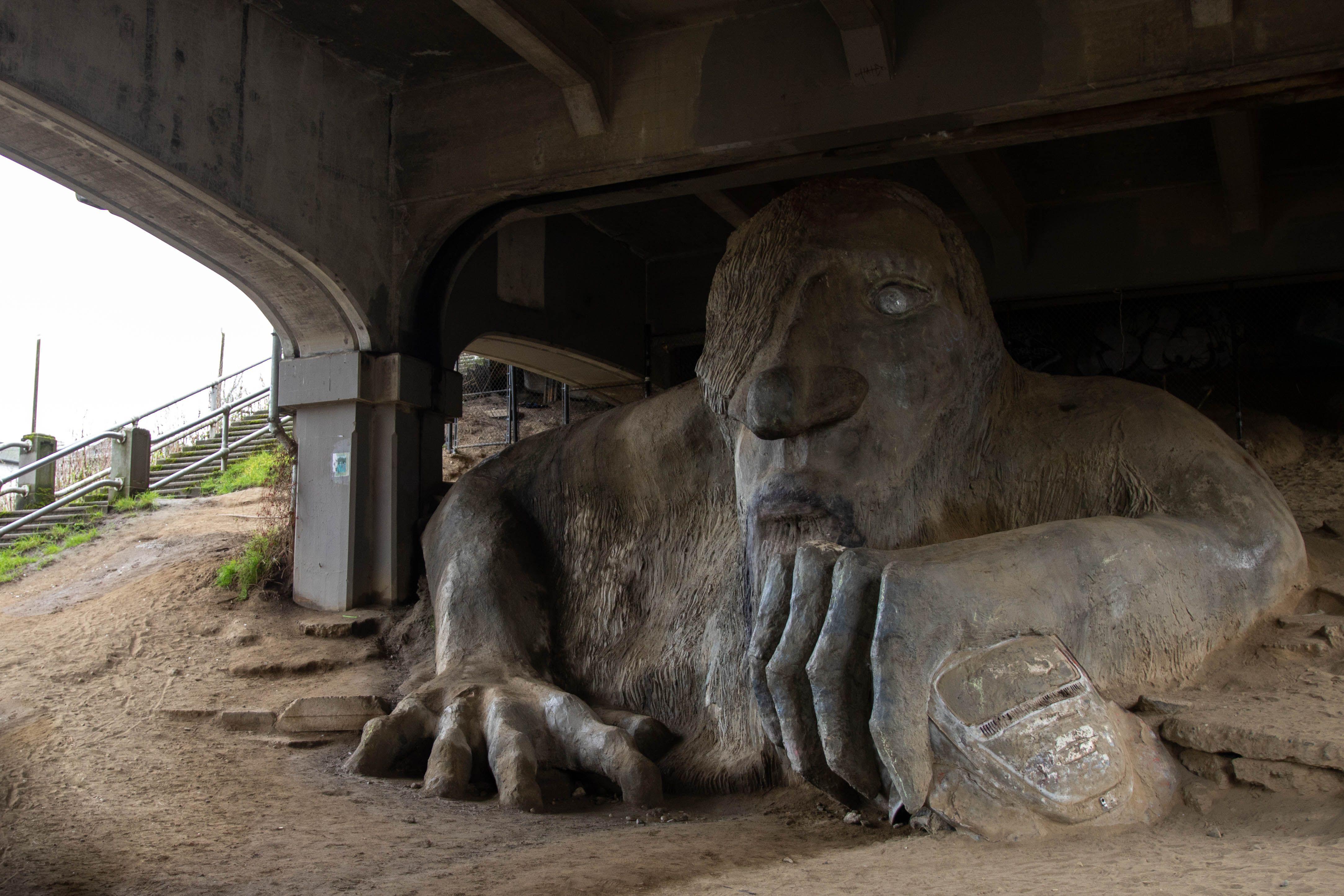 Escultura grande debajo de un puente de un monstruo sosteniendo un auto