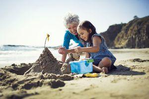 Vacation with grandchildren, grandma and grandchild playing on the beach