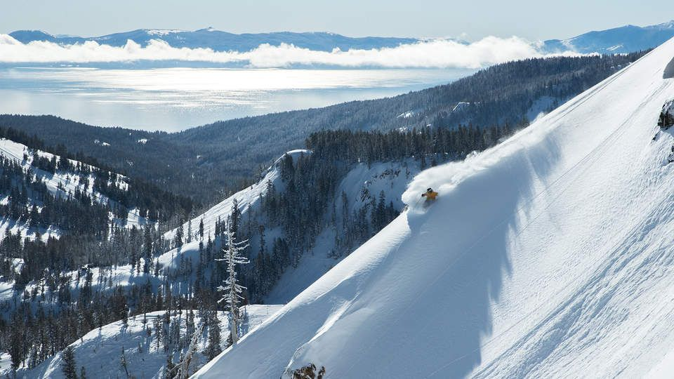 Skiier going down a mountain with tree-covered mountains in the background and lake tahoe in the distance