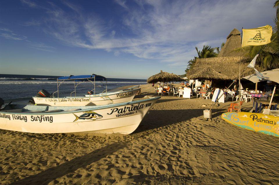 Pangas descansando en la playa de Sayulita en la hora dorada antes del atardecer, Riviera Nayarit, México
