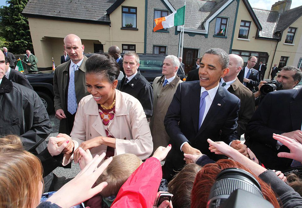 U.S. President Barack Obama and First Lady Michelle Obama greet the locals in his ancestral home of Moneygall alongside First Lady Michelle Obama (L) on May 23, 2011 in Moneygall, Ireland. U.S. President Obama is visiting Ireland for one day at the start of a week long tour of Europe. He will meet with distant relatives in Moneygall and speak at a rally in central Dublin after a concert.