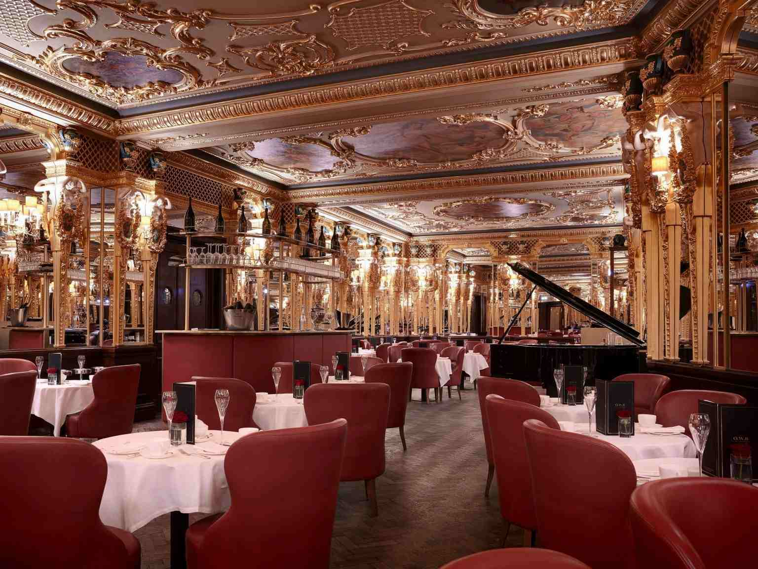 View of tables, chairs, and piano at the Oscar Wilde Lounge inside the Hotel Cafe Royal/