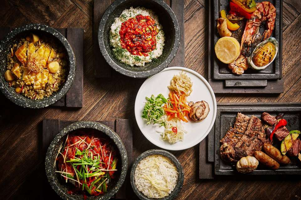 Assortment of korean dishes in stone bowls and plates