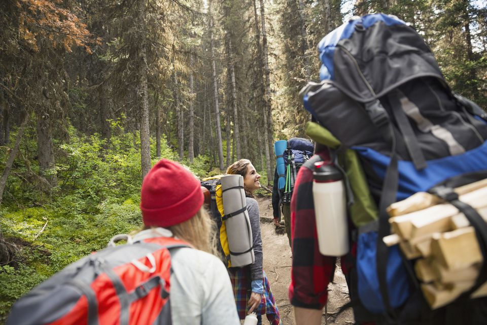 efe5f923672a Friends with backpacks and camping equipment hiking on trail in woods