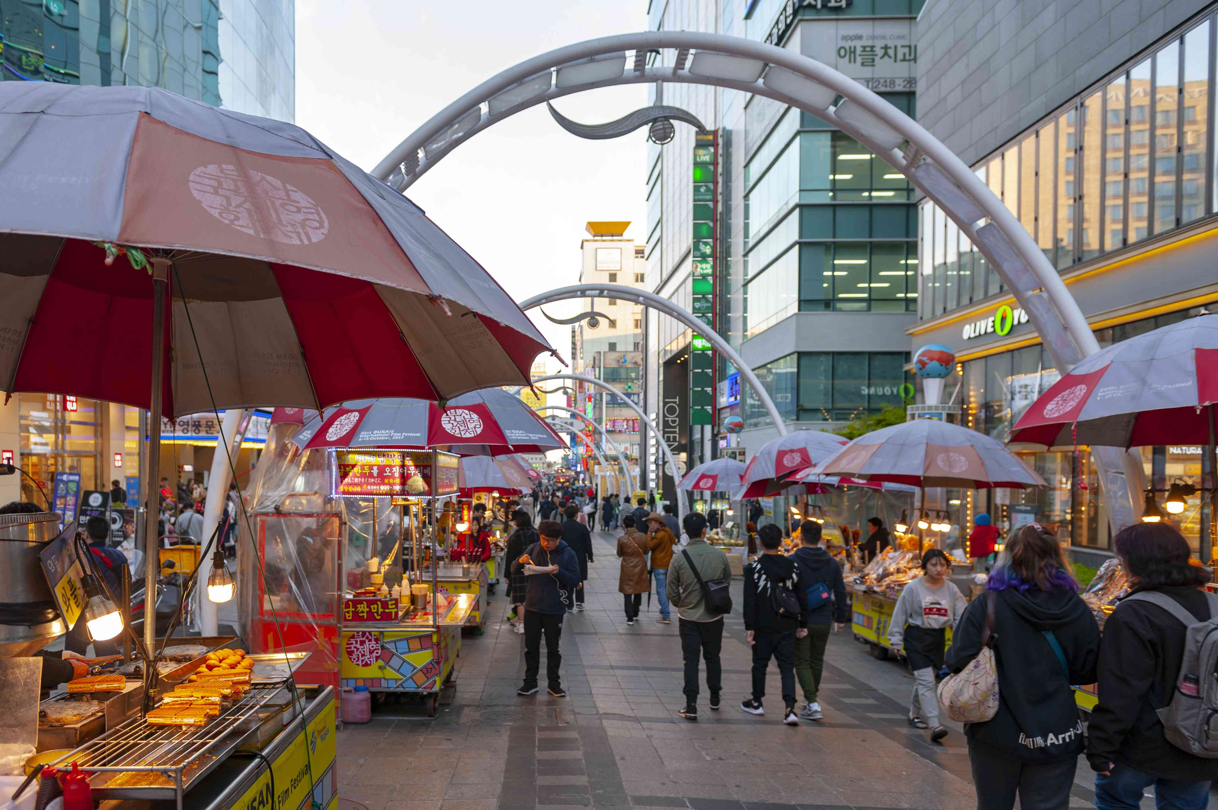 Wide walkway lined with street food carts in Busan