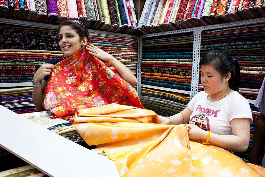A tourist shops for fabric in the South Bund Fabric Market, famous for fabrics and cutting suits, in Shanghai, China. (
