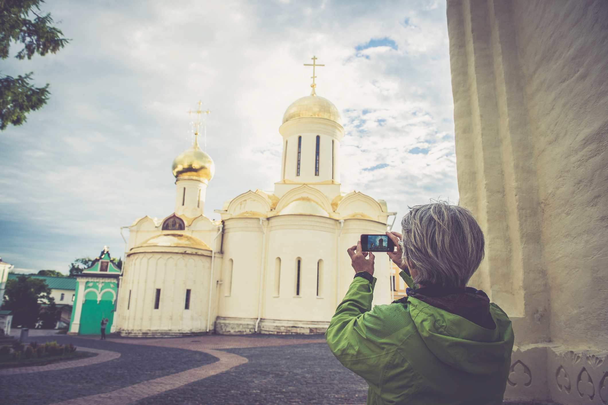 Mujer madura fotografiando la iglesia en Sergiyev Posad, parte de la ciudad de Golden Ring Cluster, Rusia
