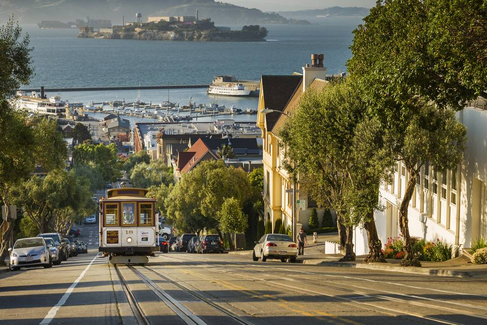 San Francisco city tram climbs up Hyde Street with Alcatraz beyond, San Francisco, California, United States of America, North America