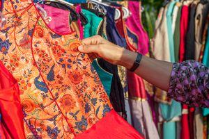 Cropped Image Of Hand Choosing Dress At Market
