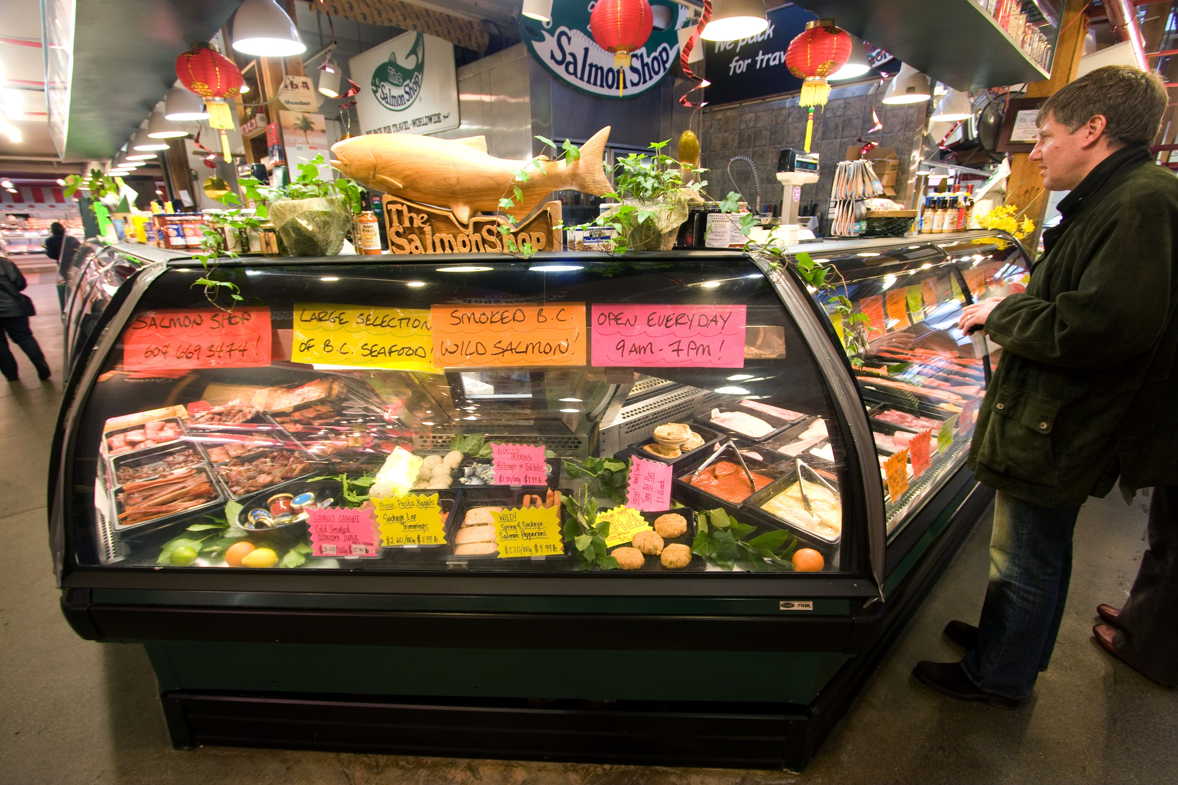 Man standing by fish counter at The Salmon Shop on Granville Island