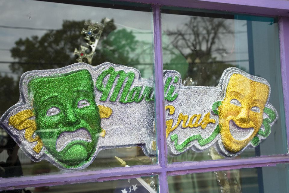 Green and yellow sign for Mardi gras with masks of comedy and drama