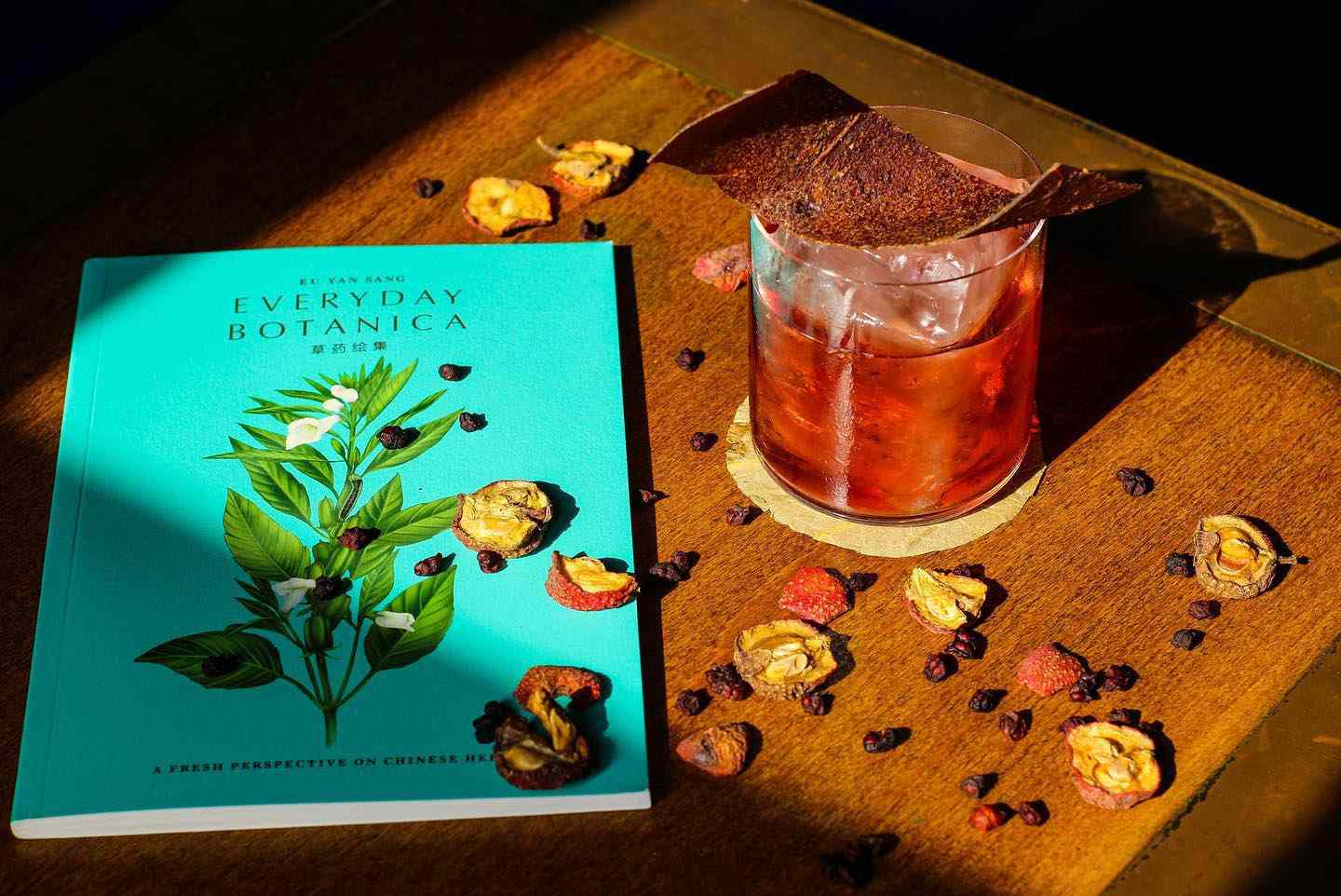Specialty cocktail sitting beside a book titled