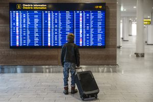 Boy with suitcase looking at airport departure board