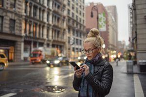 Female tourist reading smartphone text on street, New York, USA