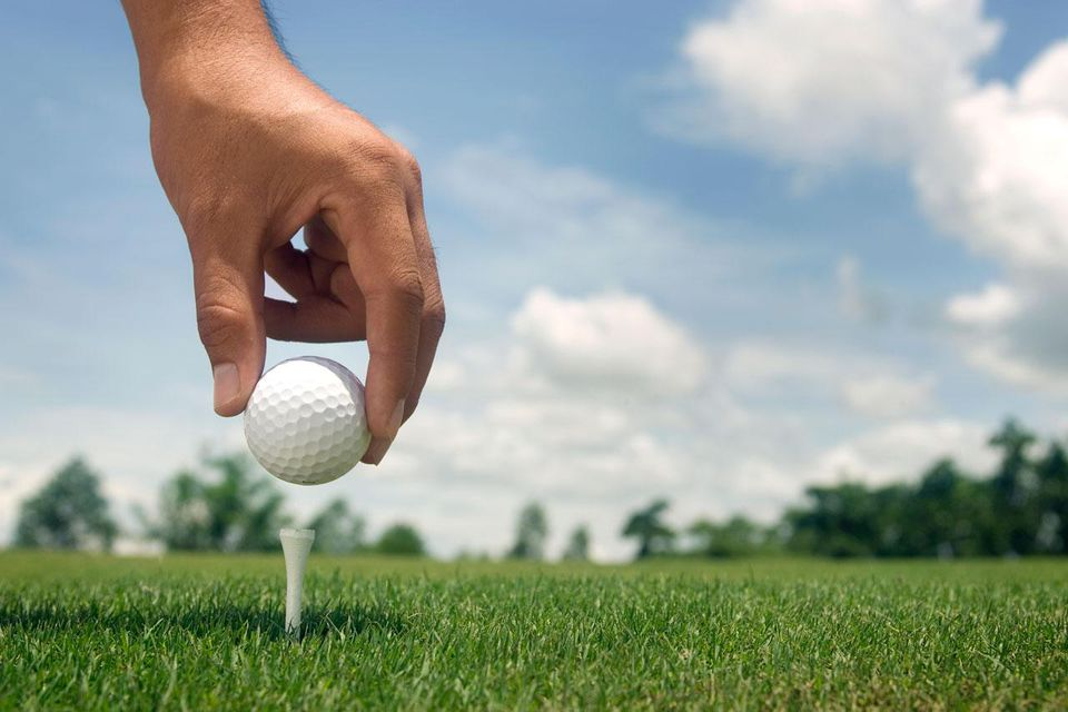 golfer placing ball onto tee