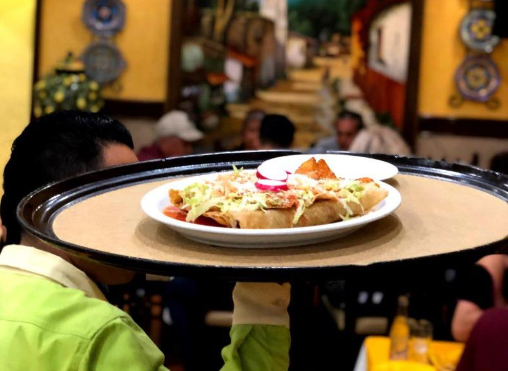 waiter holding a large black tray with a plate of enchilada on it