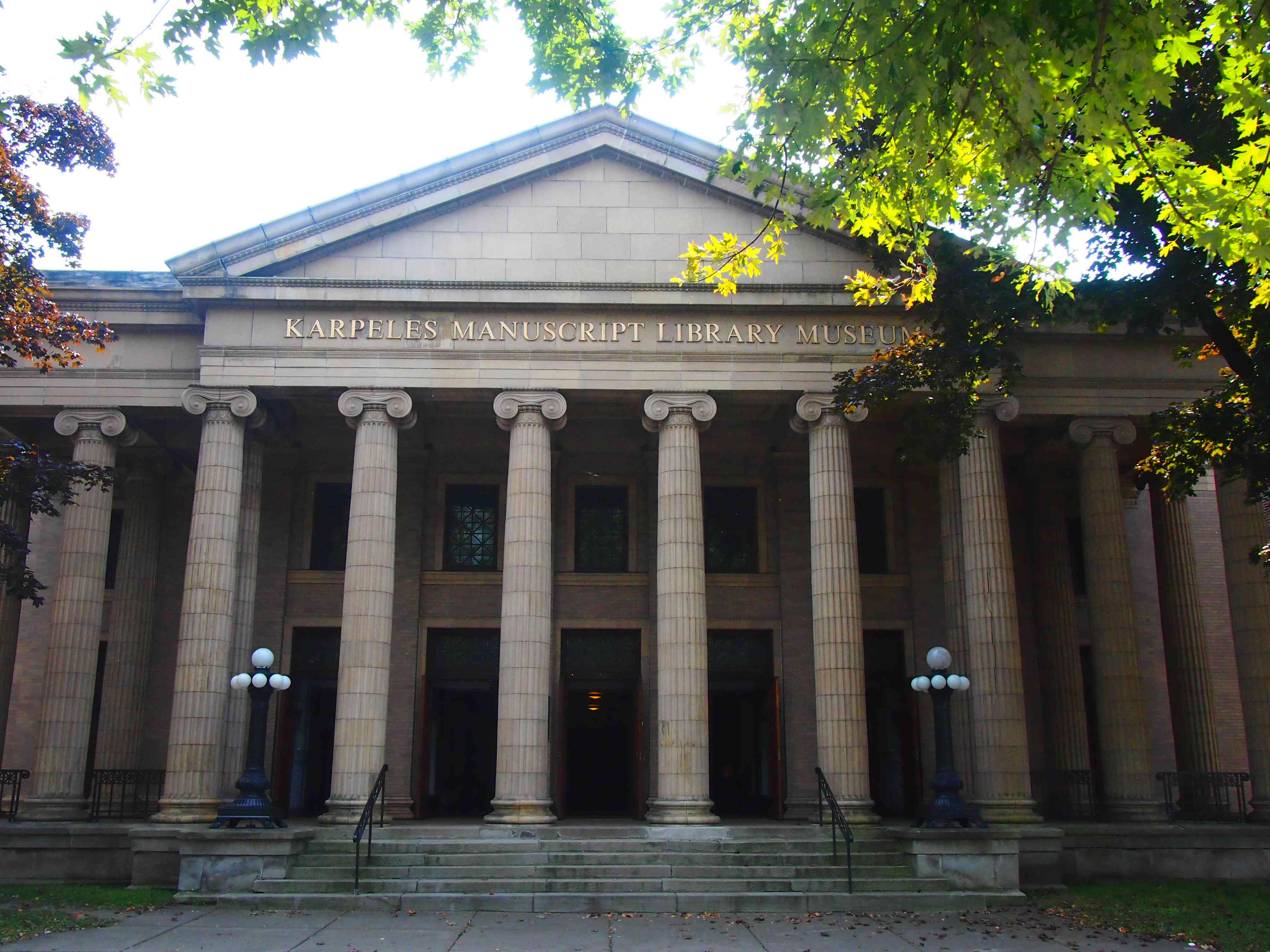 neo-classical building with columns and pointed roof and green leaves in foreground