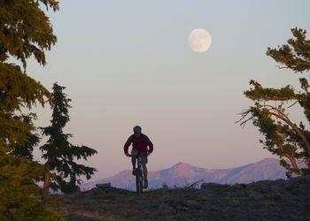 A man bikes beneath the full moon above Lake Tahoe in California.