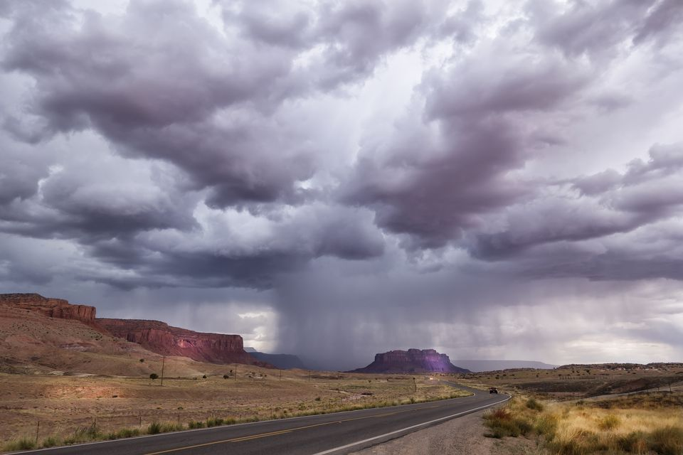 Storm clouds raining on rock formations in desert landscape