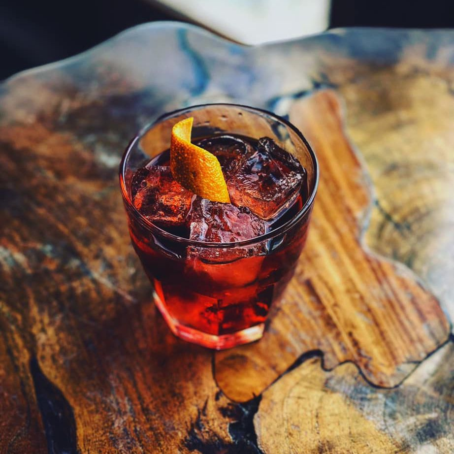 Old fashioned with a orange peel on a natural wood table