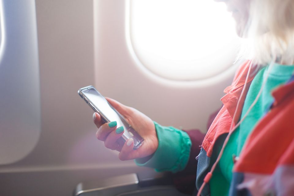 A woman holding a phone on an airplane
