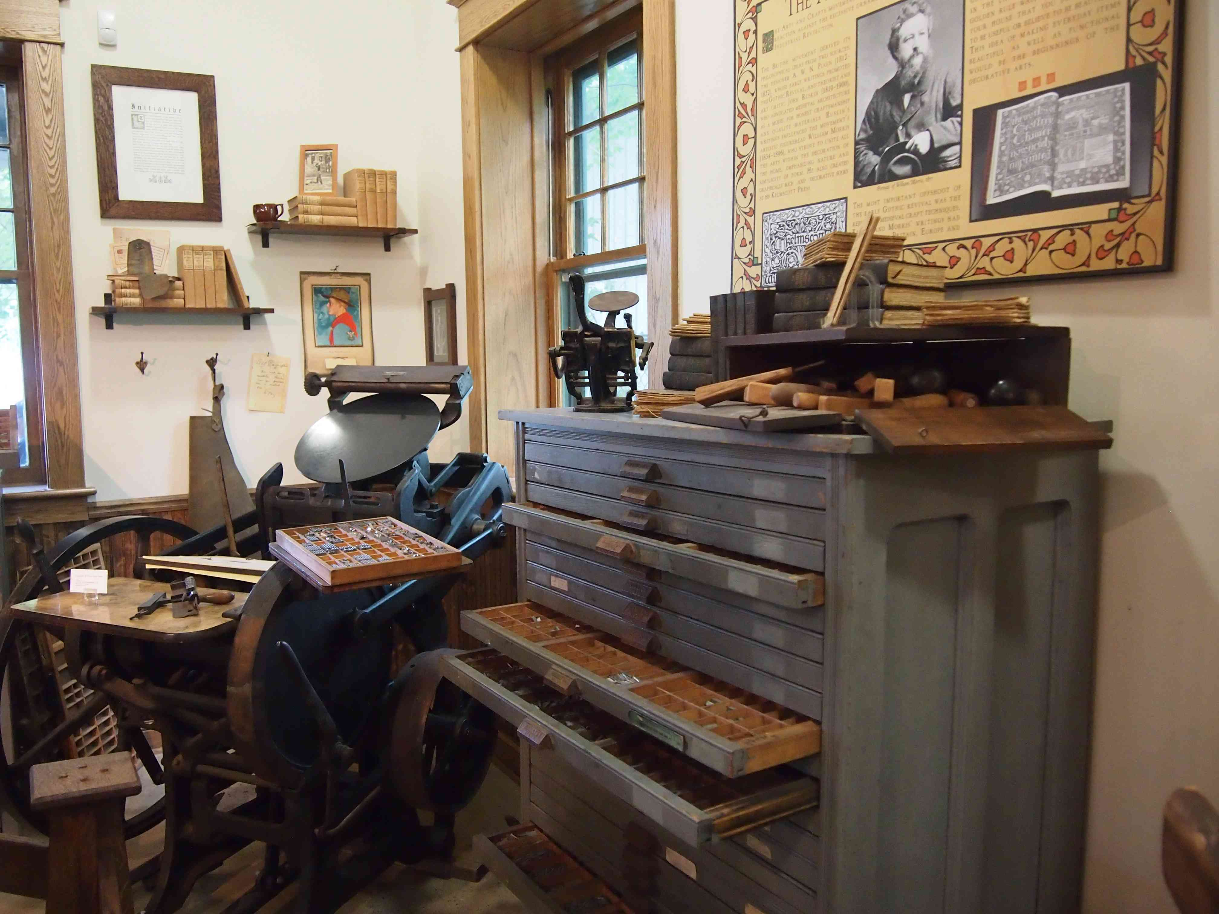 room in a museum with printing press equipment and pictures on the wall