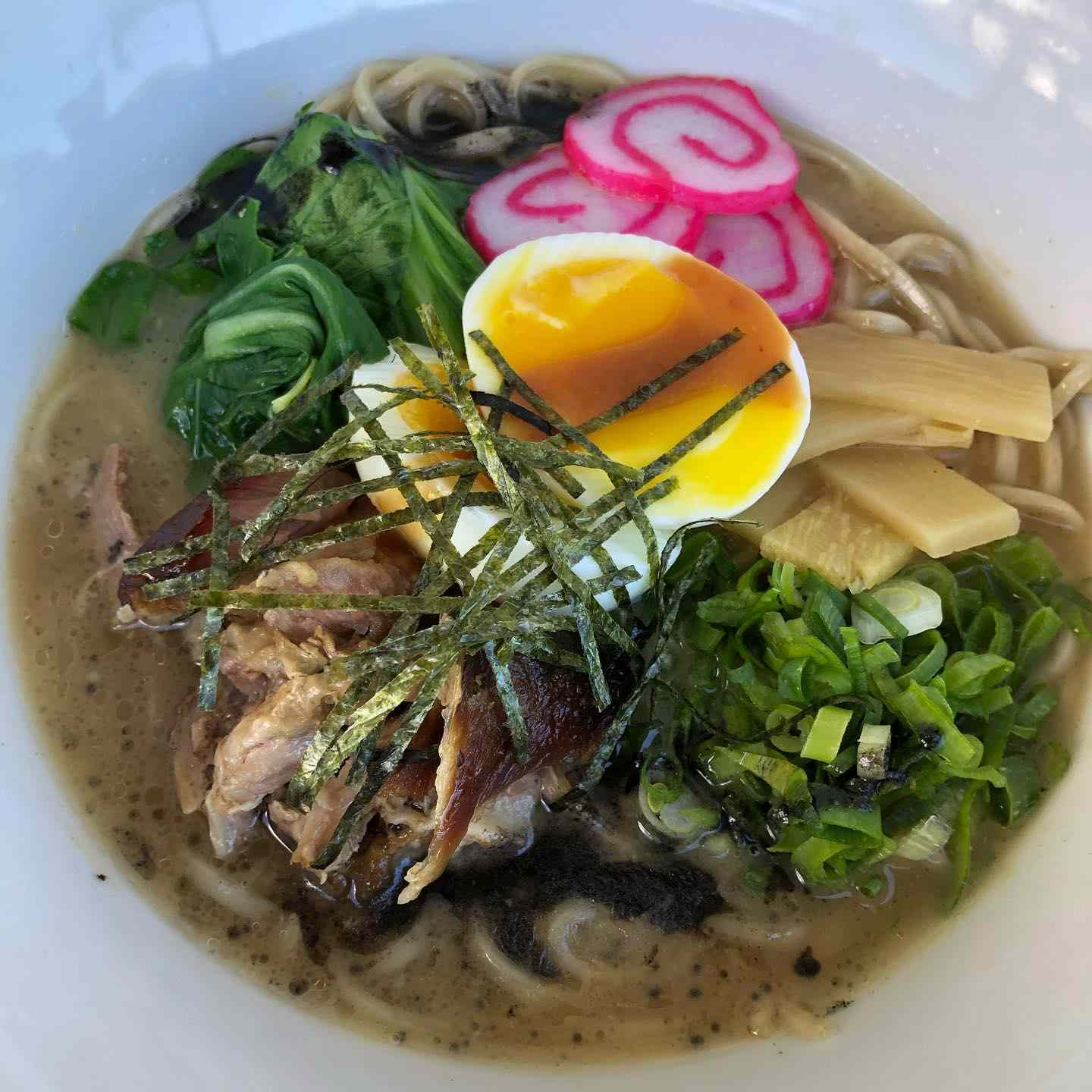 bowl of ramen from Star Noodle with a soft boiled egg, bamboo shoots, chopped scallions, red and white fish cake, bok choy, pork and shredded nori