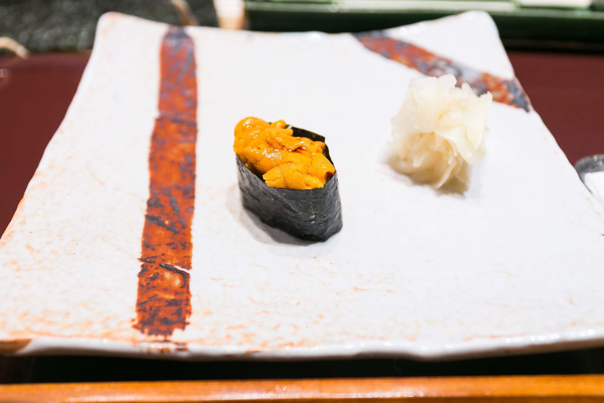 Sea urchin sushi and pickled ginger on a square plate