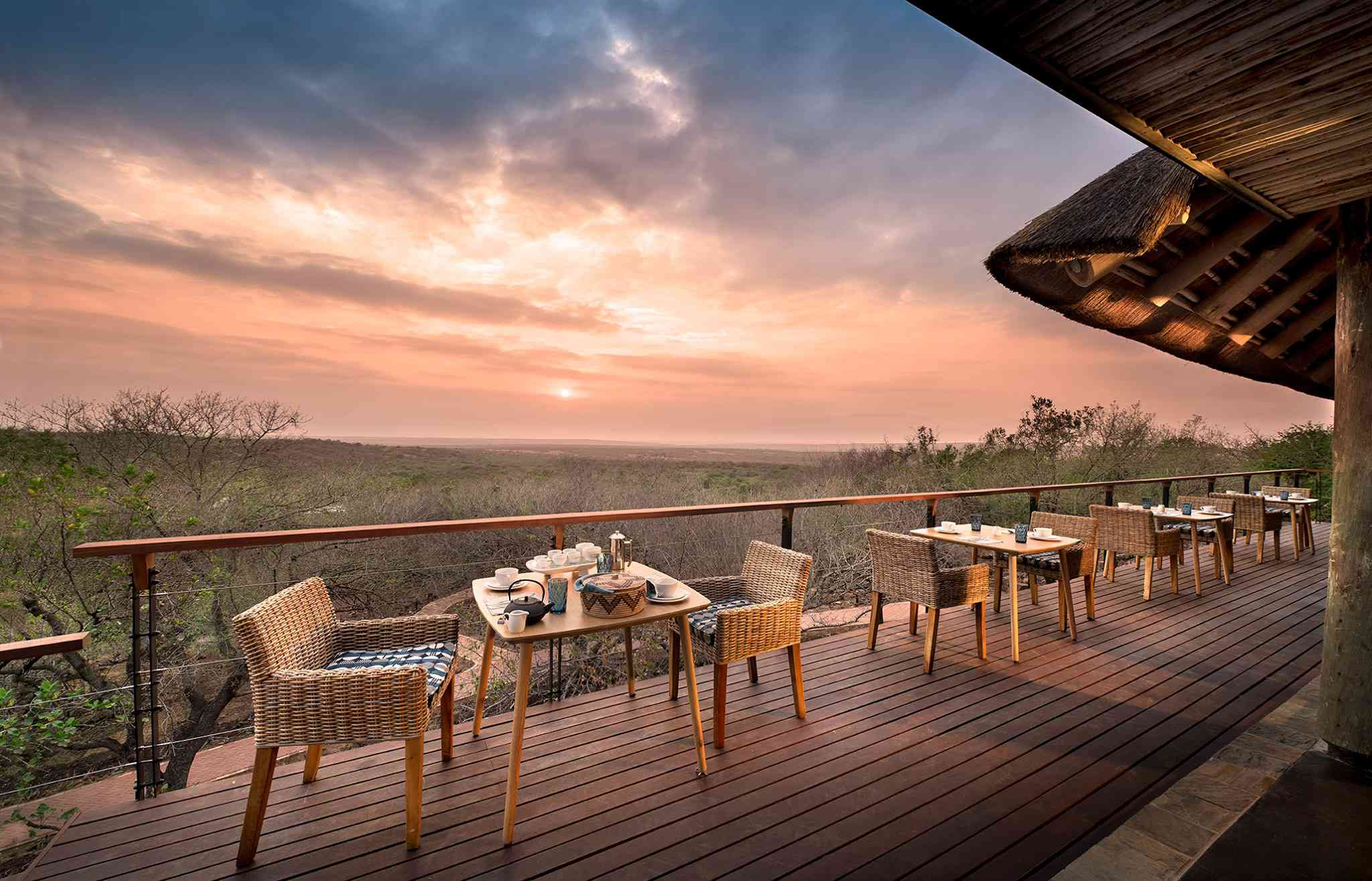 ding tables on a deck over looking Phinda Private Game Reserve at sunset