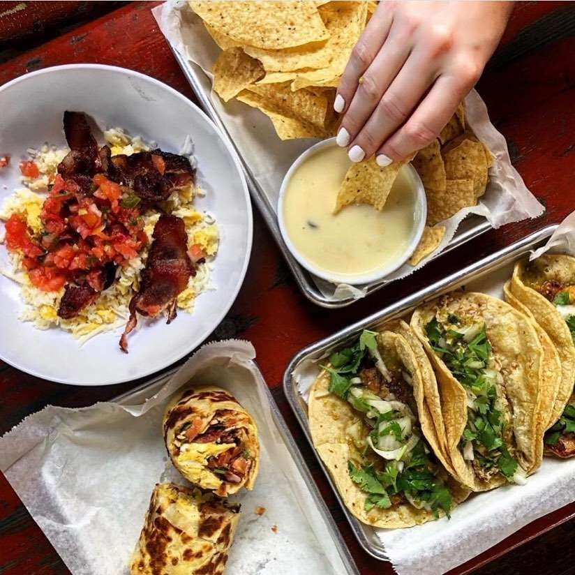 Overhead shot of a breakfast burrito cut in half, three tacos, chips and queso with a hand dipping a chip into the sauce, and a bowl of scrambled eggs, rice bacon and salsa