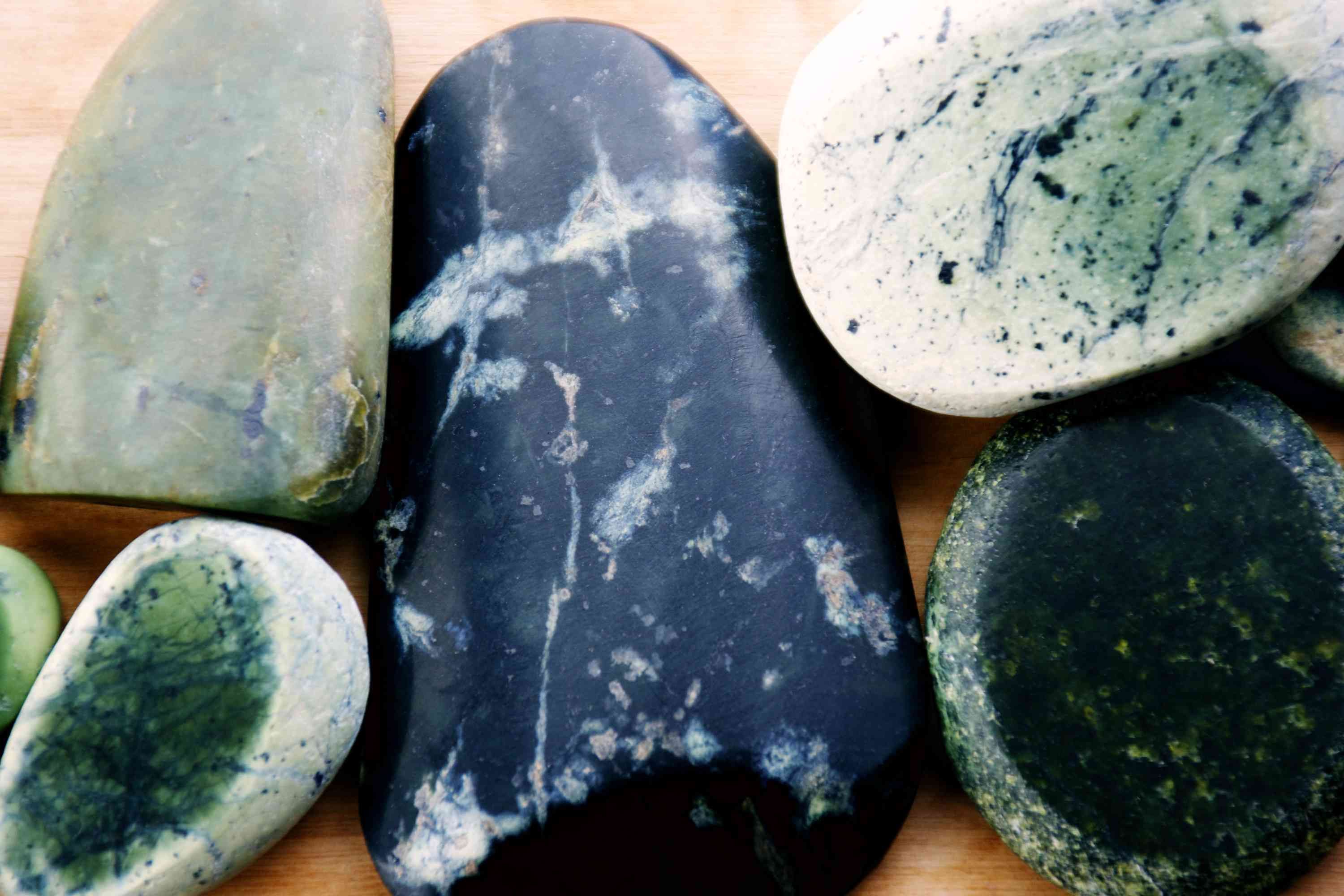 large pieces of pounamu (jade) stone of different shades of green, white, and black
