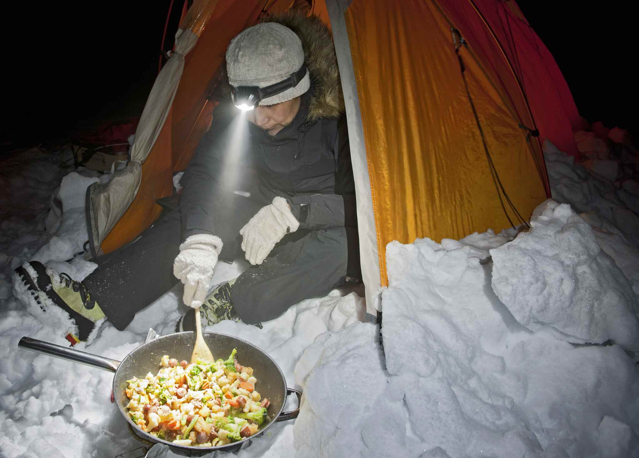 Mature woman cooking outside tent at night, Langjokull glacier, South Iceland