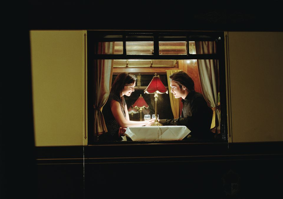 Young couple at table aboard train, exterior view, night