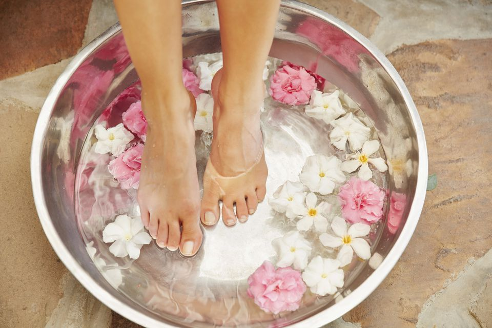woman soaking feet in spa bath