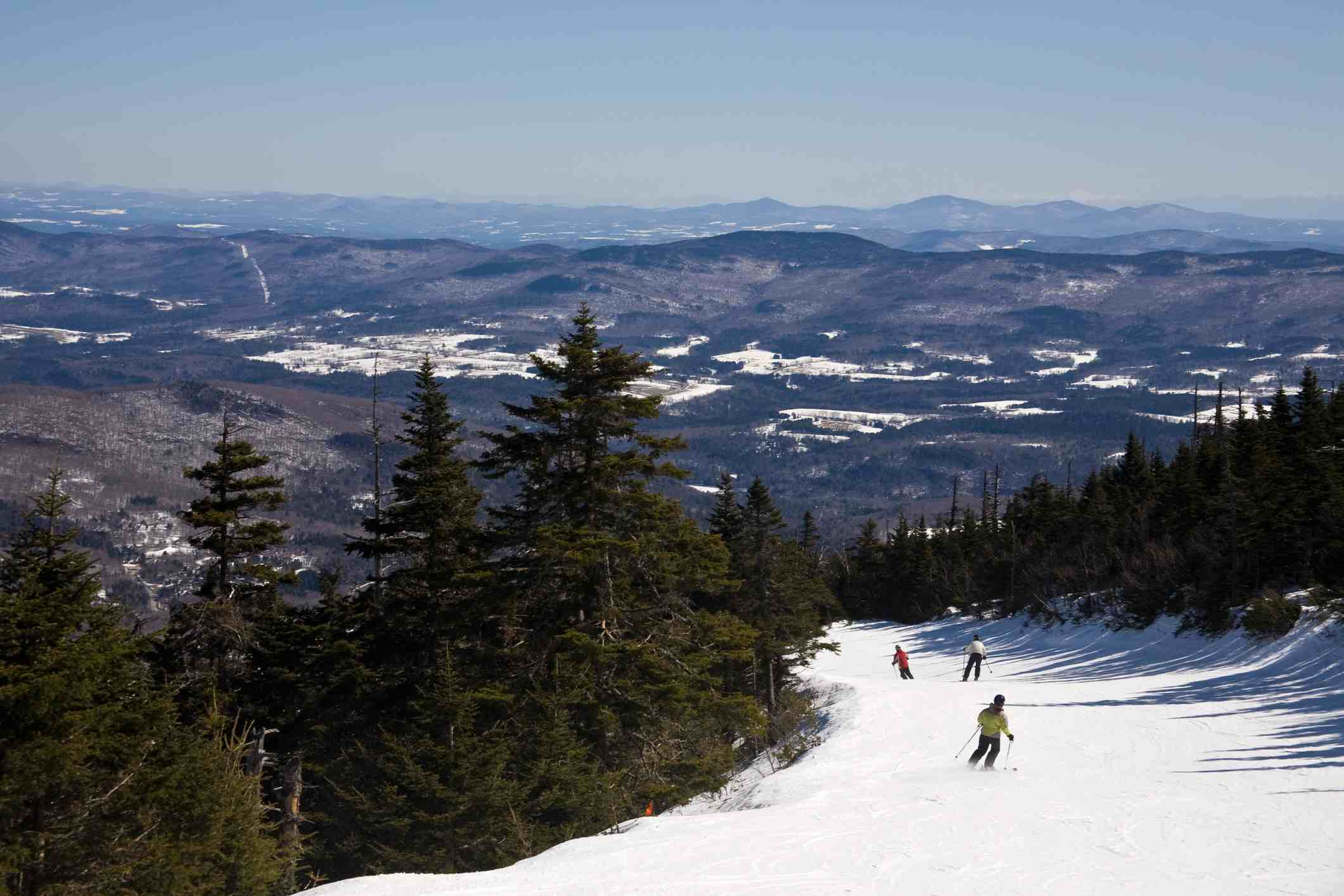 Three people ski down from the summit of Sugarbush on a trail called Jester