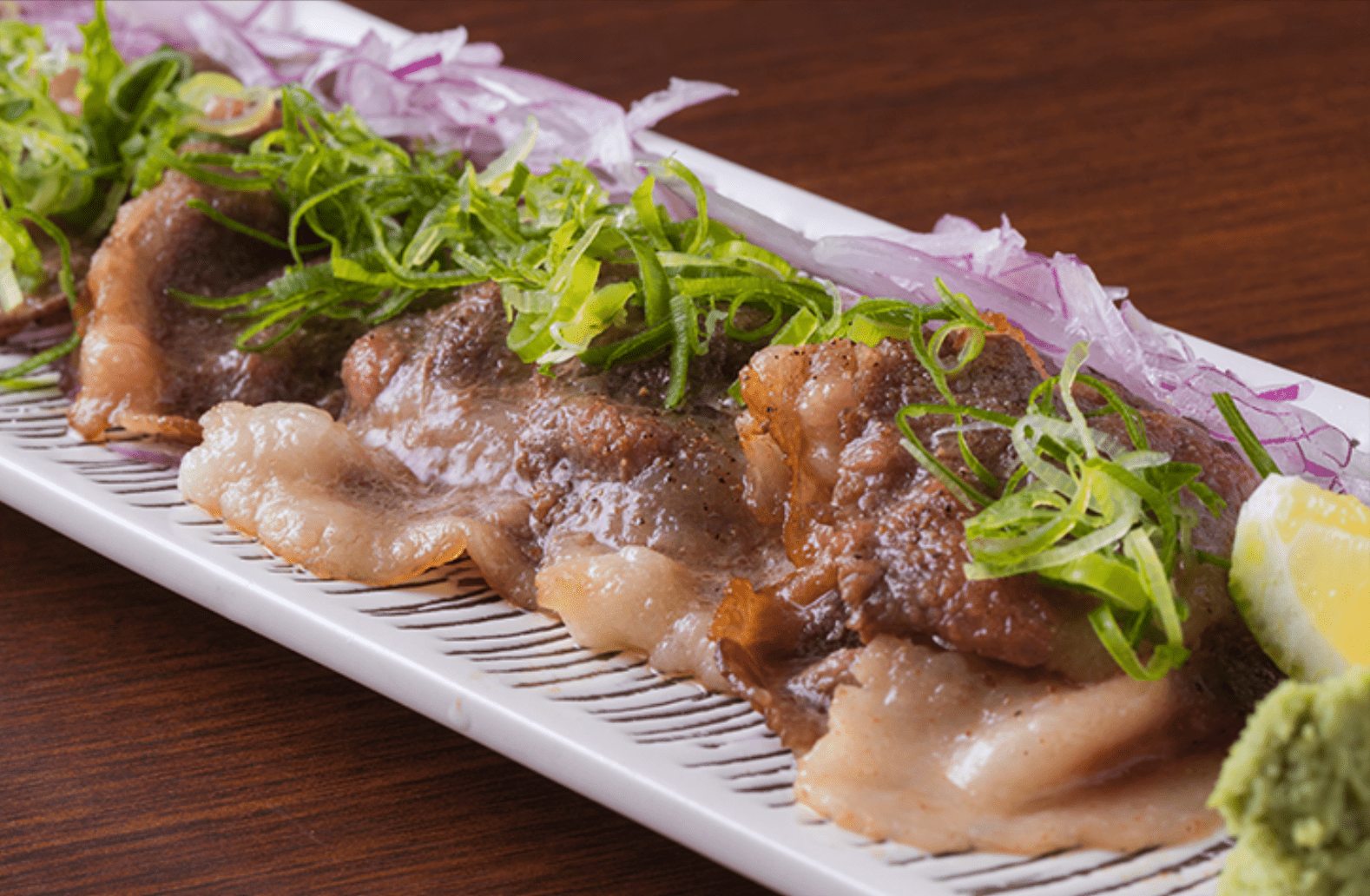 Grilled pieces of beef garnished with scallions and red onion