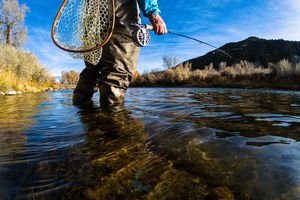 shot of a man from the waist down Fly Fishing on Scenic River