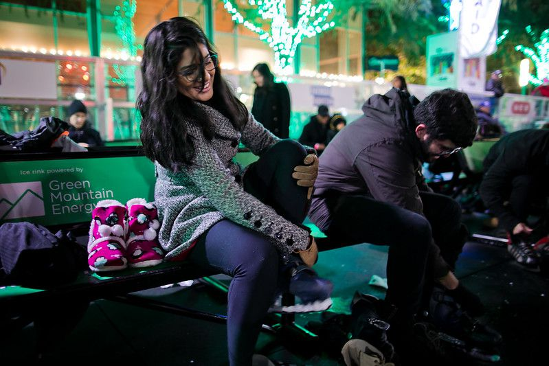People strapping into ice skates at Discovery Green
