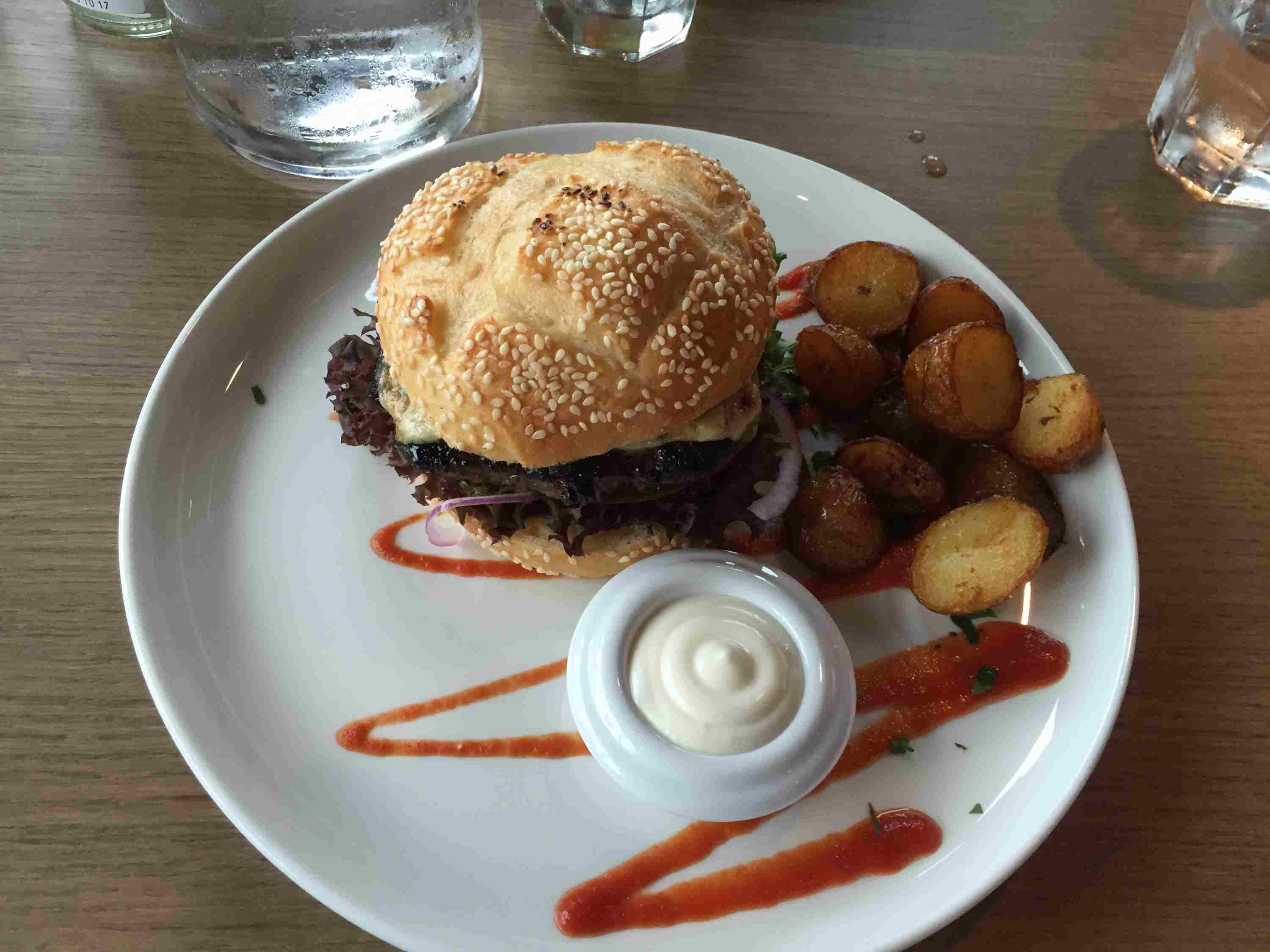 Burger on plate with potatoes and side of white sauce