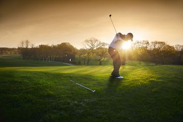 golfer in action at sunset on the green
