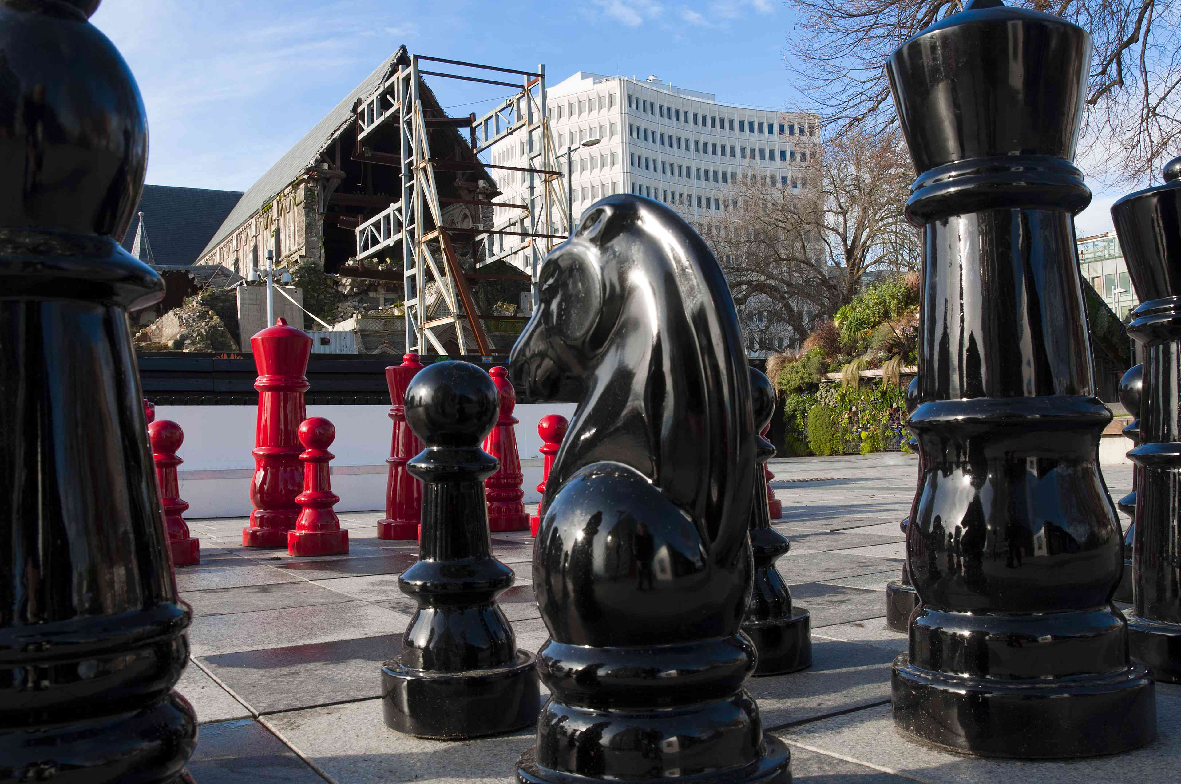 large outdoor chess pieces with scaffolding around an old church building in background