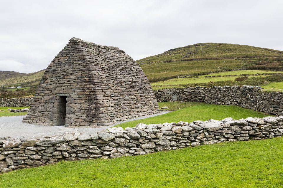 Gallarus Oratory stone church against green hills in Ireland