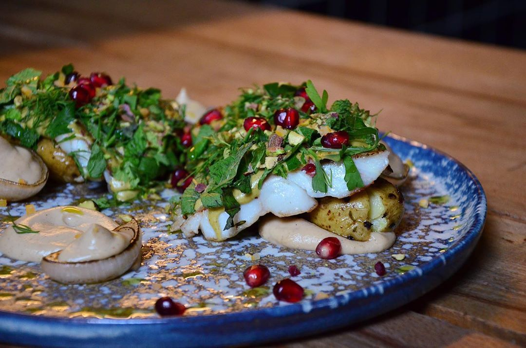 pistachio-crusted cod with small potatoes and onion on a blue and gray plate, garnished with pomegranate seeds, and a green sprount