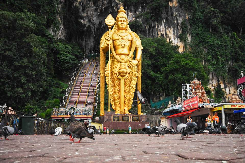 Large golden statue in front of the stairs to the Batu Caves