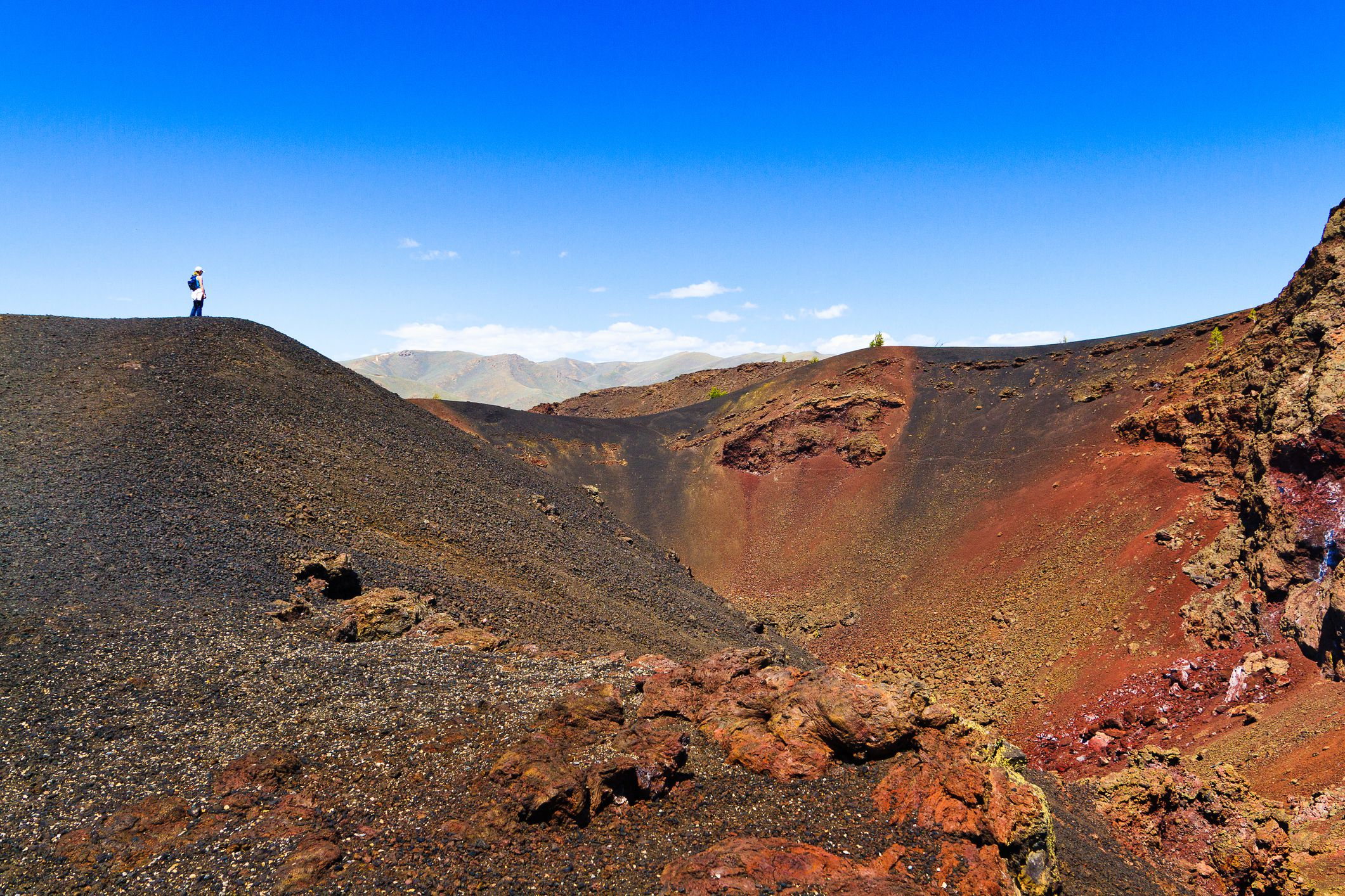 Hiker stands on hill at Craters of the Moon, Idaho