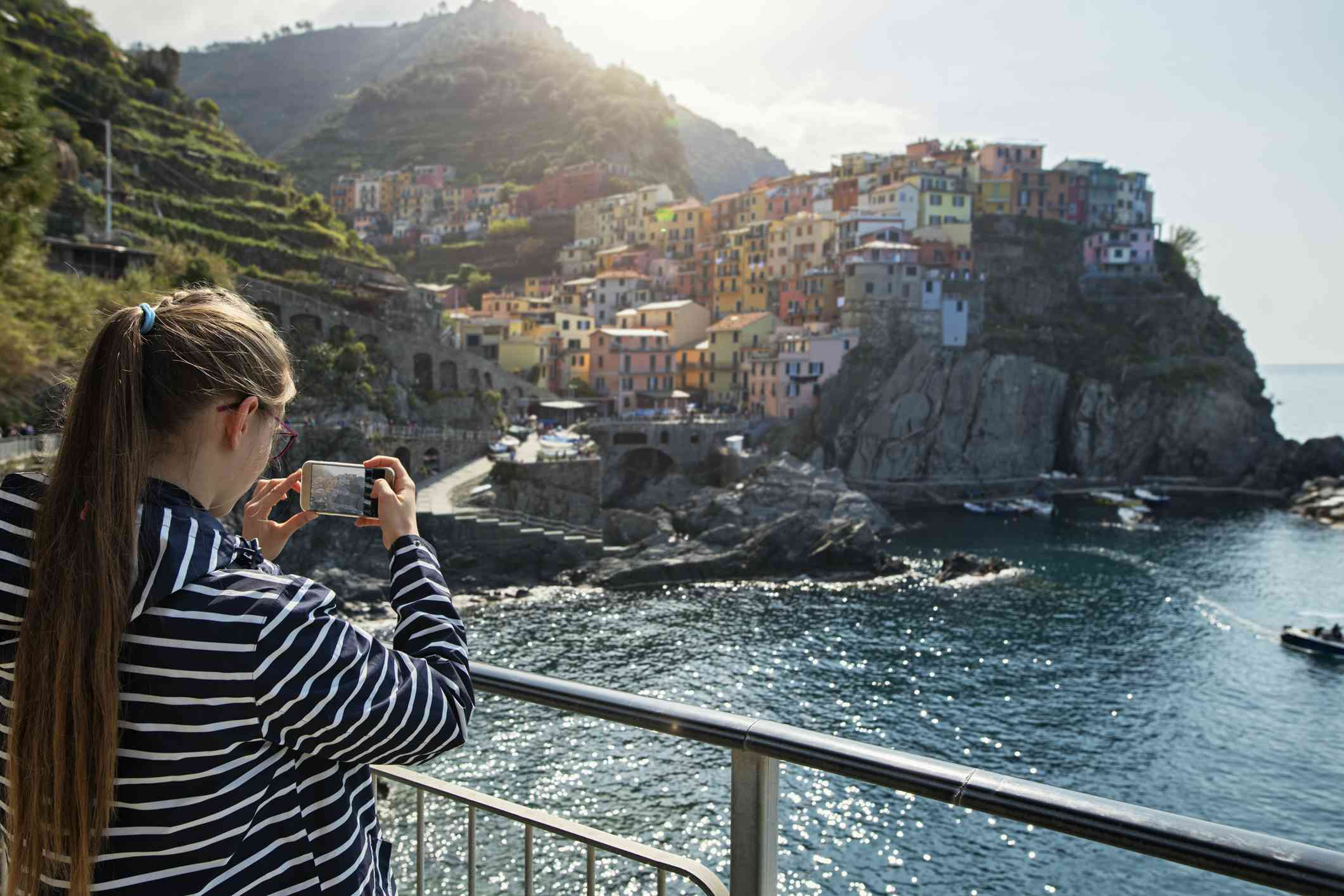 Young woman taking a picture at the Manarola Scenic Viewpoint